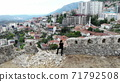 woman traveller investigating old ruins in ancient castle, discover history, aerial shot from drone above, in albania, kruje city 71792508