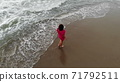 woman in a dress walking into the water by sand beach on the seaside on sunset, inspirational freedom happy holidays concept, aerial shot from drone, view from above 71792511