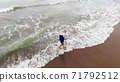 woman in blue dress walking into the water by sand beach on the seaside on sunset, inspirational freedom happy holidays concept, aerial shot from drone, view from above 71792512
