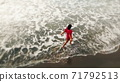 woman in red dress walking into the water by sand beach on the seaside on sunset, inspirational freedom happy holidays concept, aerial shot from drone, view from above 71792513