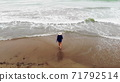 woman in a dress walking into the water by sand beach on the seaside on sunset, inspirational freedom happy holidays concept, aerial shot from drone, view from above 71792514
