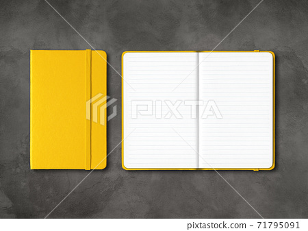 Yellow closed and open lined notebooks on dark concrete background 71795091