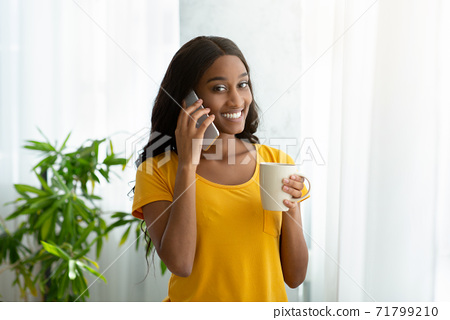 Millennial black woman speaking on cellphone and drinking coffee near window at home 71799210