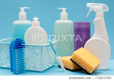 Bottles of dishwashing liquid in basket, sponges and brushes on blue background. 71801588