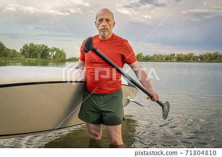 senior paddler with his stand up paddleboard 71804810