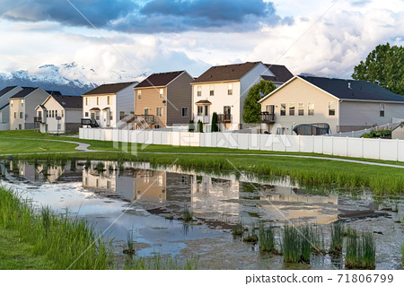 Homes and cloudy sky reflected on the shiny surface of a grassy pond 71806799