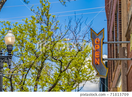 Lamp post and building with an Open sign against vibrant trees on a sunny day 71813709
