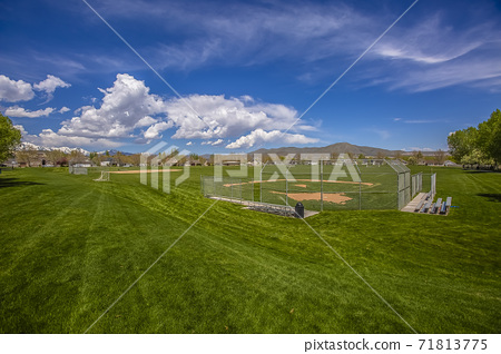 Soccer field and ballpark with trees and houses on the perimeter of the field 71813775