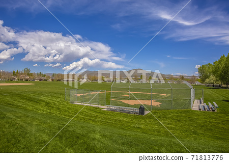 Baseball or Softball field with bleachers outside the safety fence 71813776