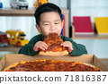 Asian boy eating pizza 71816387