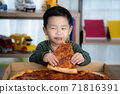 Asian boy eating pizza 71816391