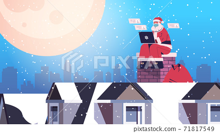 santa claus in mask sitting on roof using laptop happy new year merry christmas holidays celebration concept 71817549