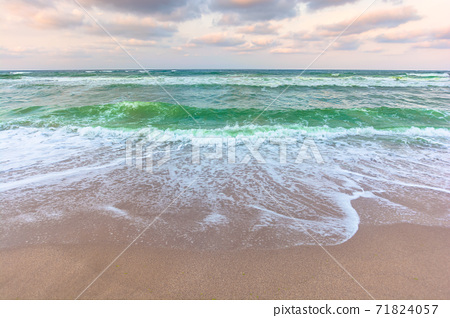 golden cloudy sunset above the green sea waters. waves crashing the sandy beach. clear horizon. changing windy weather 71824057