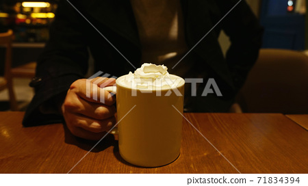 A man tries to drink a latte with whipped cream 71834394
