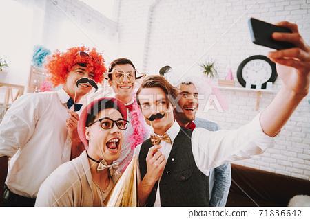 Gay guys in bow ties taking selfie on phone.  71836642