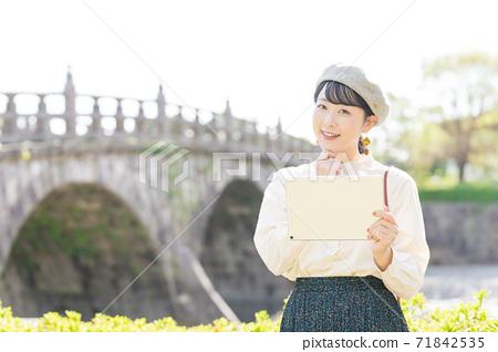 女人在旅遊區裡拿著平板電腦 71842535