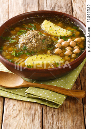 Homemade Kufta bozbash is a traditional Azerbaijani meatball soup and chickpea close-up in a plate. Vertical 71846589