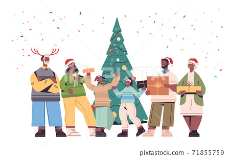 multi generation family in santa claus hats holding wrapped gift boxes happy new year and merry christmas holidays 71855759