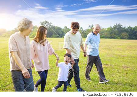 three generation asian family walking  in the park 71856230
