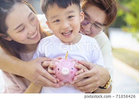 happy parent holding piggy bank and teaching son save money 71856426