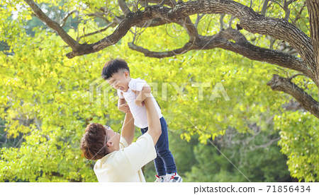 father rising up his son and playing in the park 71856434