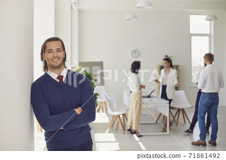 Happy businessman or company worker standing in office looking at camera and smiling 71861492
