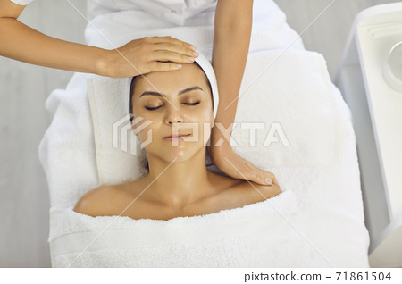 Woman with her eyes closed lies in a spa and receives a facial massage with the hands of a masseur. 71861504