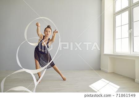 Young rhythmic gymnast rehearsing movements with ribbon on warm floor in modern studio 71861549