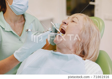 Dentist looking her old patient with tools 71861916