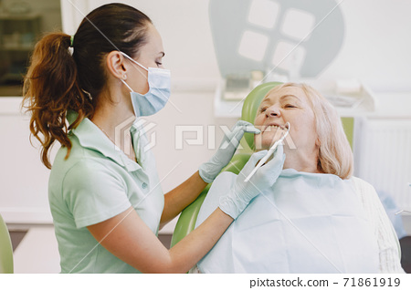 Dentist looking her old patient with tools 71861919