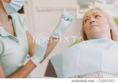 Dentist looking her old patient with tools 71861971