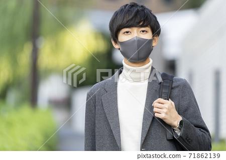 회색 천 마스크를 쓴 젊은 남성의 천 마스크를 쓴 젊은 남성 71862139