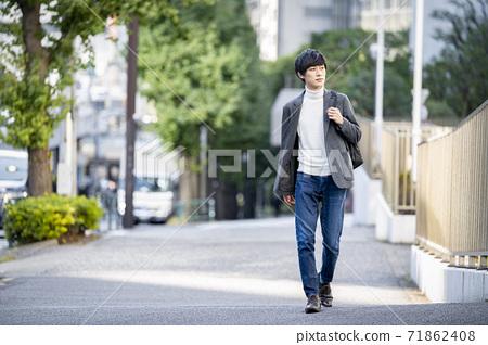 走在有背包的人行道上的年輕人 71862408