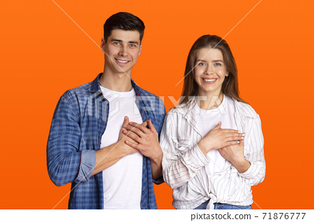 Grateful gesture concept. Pretty smiling young male and female in casual clothes keep hands on chest, being thankful 71876777