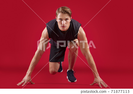 Full length portrait of athletic young runner standing on start over red studio background 71877113
