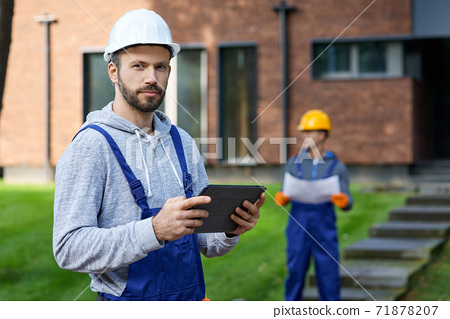 Portrait of young male builder looking at camera while holding digital tablet pc with coworker working in the background at cottage construction site 71878207