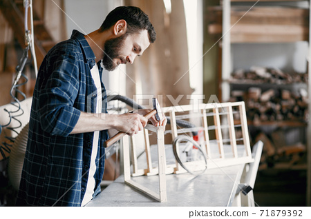 Carpenter hammering a nail in a workshop 71879392