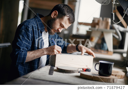 Man in the workshop with a wood 71879427