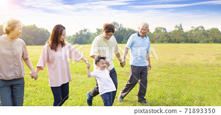 three generation asian family walking  in the park 71893350
