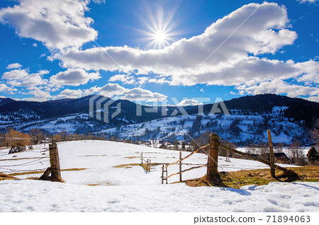 mountainous rural landscape on a sunny winter day. fields and trees on rolling hills covered in snow. fluffy clouds on the sky. beautiful carpathian landscape 71894063