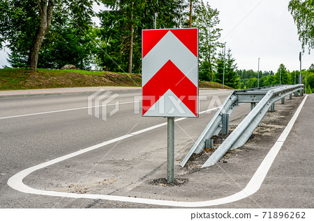 a metal safety barrier with a red and white striped traffic sign 71896262