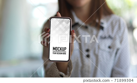Close up view of female showing smartphone in blurred background 71899304