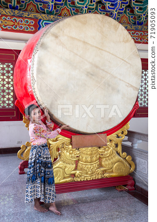 A young woman with traditional drum in Buddhist temple, Thailand 71905093