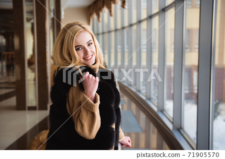 beautiful girl looks through the window of the business center 71905570