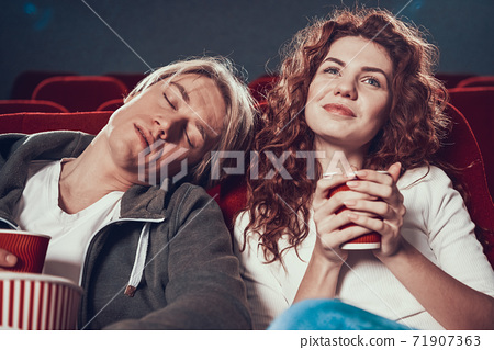 Young blond man fell asleep in movie theater. 71907363