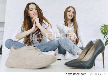 Stylish girls sitting on the floor in a dressing room with shoes 71911728