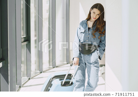 Girl at home near overloaded suitcase 71911751