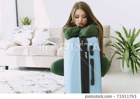 Woman prepare travel suitcase at home 71911763