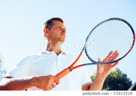 Young man tennis player checks his racket to start a game 71913526