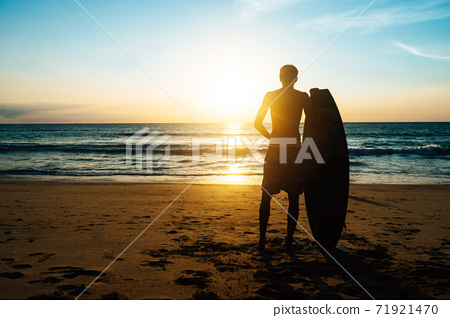 Silhouette of surfer man carrying their surfboards on sunset beach with sun light. 71921470